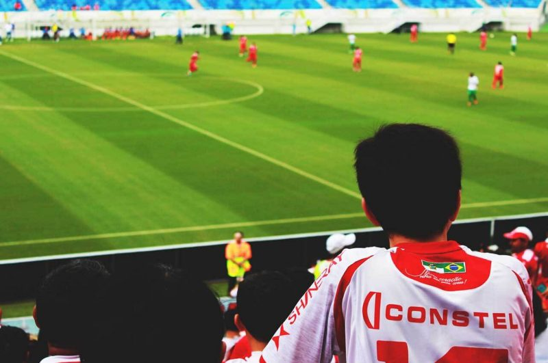 White and Red Jersey Shirt Looking at Sport Game